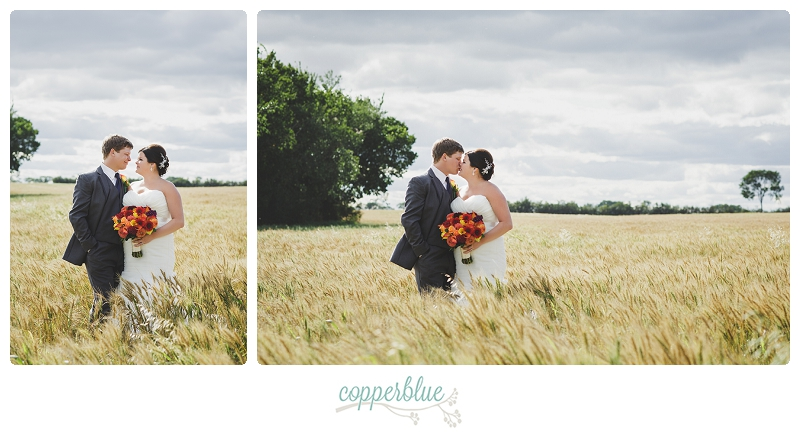 Bride and groom in field of wheat
