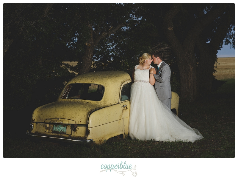 Bride and groom with old car